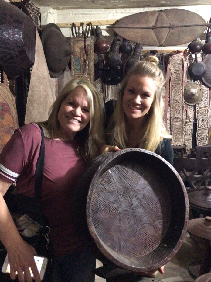 "Diana and Bree holding a traditional serving to hold the large circular ""injera"" with different stews spooned around the flatbread—eaten with fingers!"